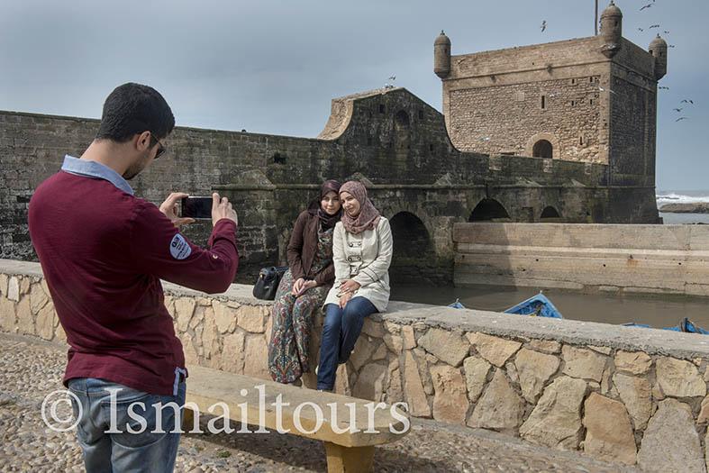 Marokko, Essaouira 20150304.  Jongen fotografeert met een mobieltje twee meisjes die voor de stadsmuur zittin in een kustplaats. Boy is taking a picture of two girls sitting in front of the city wall. Culturel heritage. Naamsvermelding verplicht; Foto ; Sabine Joosten/Hollandse Hoogte